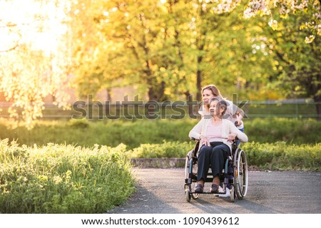Elderly grandmother in wheelchair with granddaughter in spring nature. #1090439612