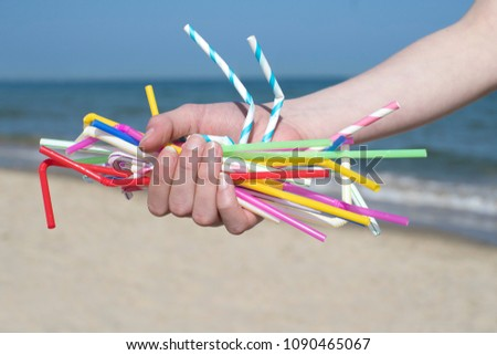 Close Up Of Hand Holding Plastic Straws Polluting Beach Royalty-Free Stock Photo #1090465067