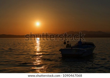 Boat in the sunset on Garda lake, Italy #1090467068
