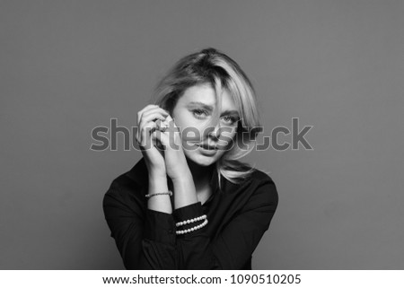 Close up portrait of a sad young woman, looking to the camera, holding hands near face, against a plain studio background #1090510205
