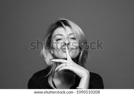 Close up portrait of a young woman, holding hand near face, finger on the lips, against a plain studio #1090510208