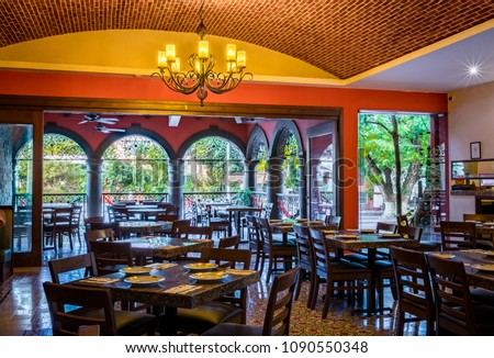 Interior of a traditional Mexican restaurant with tables and chairs, brick ceiling and chandellier #1090550348