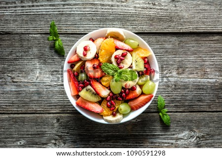 Fresh fruit salad, top view in a bowl on wooden background, vegetarian food concept #1090591298