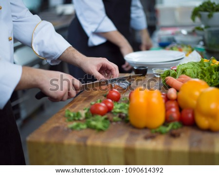 Chef hands preparing marinated Salmon fish fillet for frying in a restaurant kitchen #1090614392