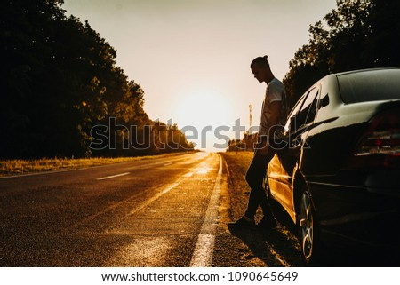 Confident young adventurer, resting leaning on his car against sunset. #1090645649