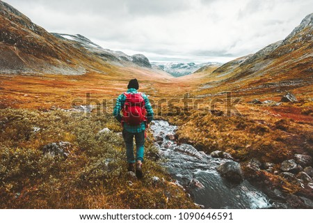 Traveling Man tourist with backpack hiking in mountains landscape active healthy lifestyle adventure vacations in Scandinavia #1090646591
