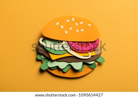 Creative conceptual art still life. Paper craft hamburger with cheese tomatoes and onions on a yellow background. Stylish composition cut out from colored paper. Illustrative close-up collage.  #1090654427