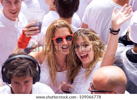 PAMPLONA, SPAIN -JULY 6: Young women are having fun at the opening of the San Fermin festival. Plaza in front of municipality. Pamplona, Navarra, Spain 6 July 2012 in Pamplona Spain. #109066778