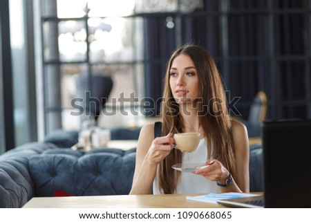 A beautiful business woman drinking cappuccino in the restaurant. Young lady drinking a hot beverage. #1090668065