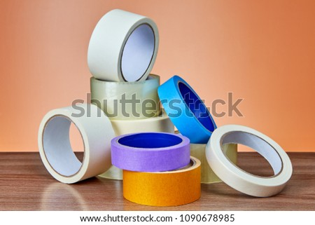 A heap of packing tape and a masking tape on an orange background. #1090678985
