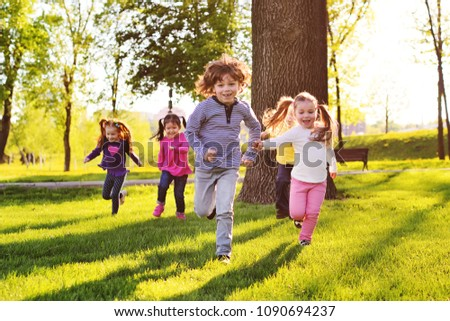 many young children smiling running along the grass in the park. Childhood, Children's Day, vacation, vacation, adventure, friendship. Royalty-Free Stock Photo #1090694237