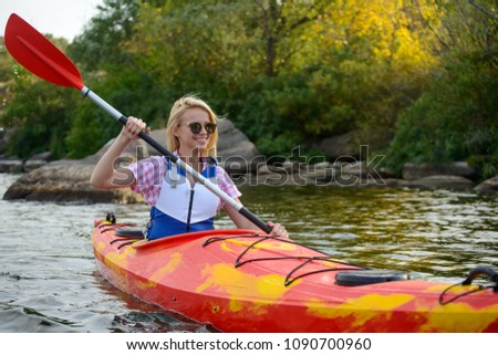 Young Woman Paddling Kayak on the Beautiful River or Lake among Stones at the Evening #1090700960