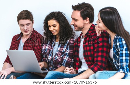 The four people with a laptop sitting on the white wall background #1090916375