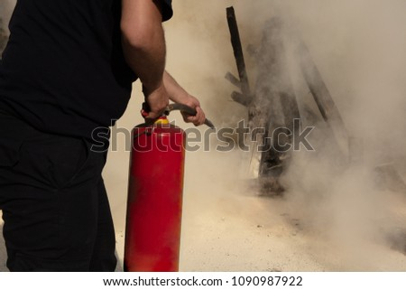 Young man pointing a powder type fire extinguisher forwards towards the fire in a serious situation #1090987922