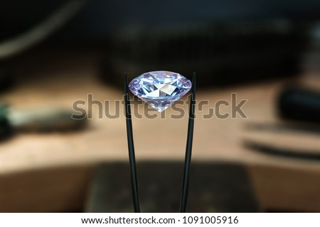 Beautiful diamond stone in tongs. Craft jewelery making with professional tools in jeweller studio. Ring repairing. Putting the diamond on the ring. Macro shot. Manufacture of jewellery. #1091005916