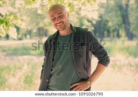 face of a bearded smiling bald man in the park. Portrait of a middle-aged man. #1091026790