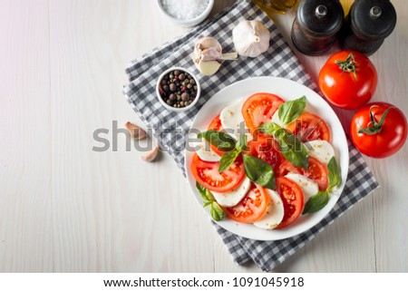 Photo of Caprese Salad with tomatoes, basil, mozzarella, olives and olive oil on wooden background. Italian traditional caprese salad ingredients. Mediterranean, organic and natural food concept. #1091045918