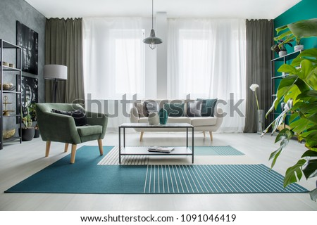 Table on carpet next to a green armchair and beige sofa in bright living room interior with plant #1091046419