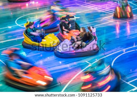 Young people driving bumper car at amusement park #1091125733