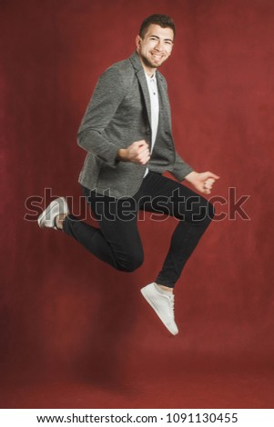 Photo of a young man on a red wall background looking at camera jumping.