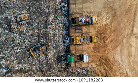 A lot of waste is disposed of in the waste disposal pits. Loaders is working on a mountain garbage. Aerial view and top view. #1091182283