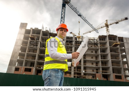 Portrait of engineer in hardhat and safety with blueprints standing against working building cranes #1091315945