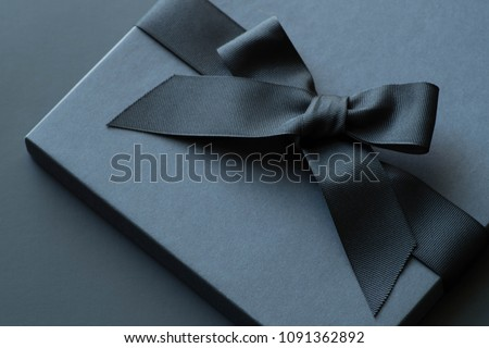 Black gift box on a dark contrasted background, decorated with a textured bow and feathers, creating a romantic atmosphere. Typically used for birthday, anniversary presents, gift cards, post cards. #1091362892