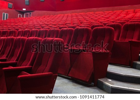 View from stairs on rows of comfortable red chairs in illuminate red room cinema #1091411774