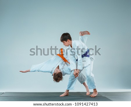 The teen boys fighting at Aikido training in martial arts school. Healthy lifestyle and sports concept. Teenagers in white kimono on white background. Children with concentrated faces #1091427413