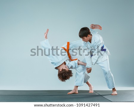 The teen boys fighting at Aikido training in martial arts school. Healthy lifestyle and sports concept. Teenagers in white kimono on white background. Children with concentrated faces Royalty-Free Stock Photo #1091427491