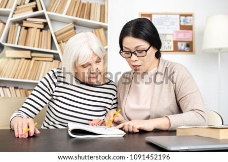 Whats wrong. Beautiful senior tutor and student looking down and checking task #1091452196