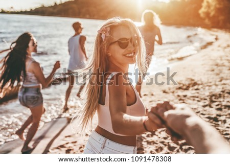 Group of young attractive friends are having fun on beach, running and smiling. #1091478308