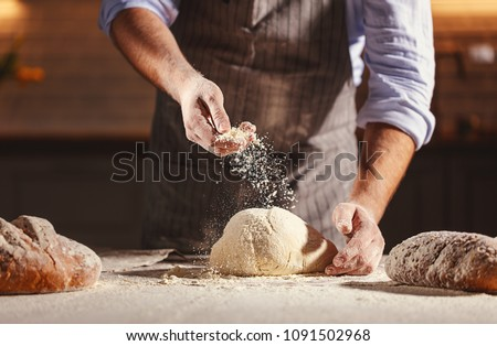 hands of the baker's male knead dough #1091502968
