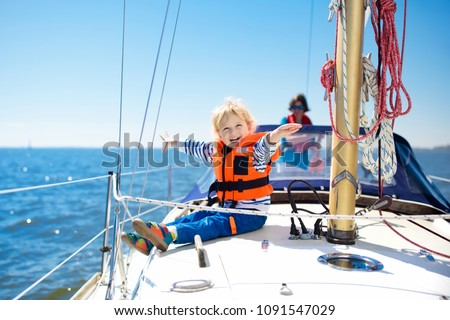 Kids sail on yacht in sea. Child sailing on boat. Little boy in safe life jacket travel on ocean ship. Children enjoy yachting cruise. Summer vacation for family. Young sailor on sailboat front deck. #1091547029