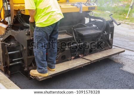Worker on Asphalting paver machine during Road street repairing works Asphalting and Repair of roads #1091578328