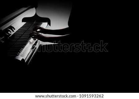 Piano player. Pianist hands playing grand piano closeup isolated on black background
