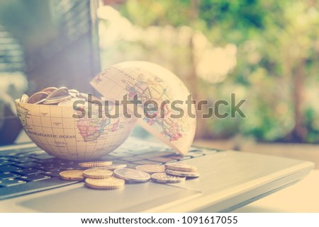 Passive income or making money / wealth from online ecommerce concept : Open globe filled with coins on a laptop, depicts new entrepreneur in new era gain more revenue or wealth from internet sales. #1091617055