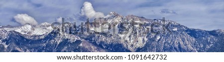 Panoramic view of Wasatch Front Rocky Mountain, highlighting Lone Peak and Thunder Mountain from the Great Salt Lake Valley in early spring with melting snow, pine trees, scrub oak and quaking aspen  #1091642732