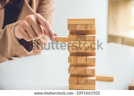 Alternative risk plan and strategy to growth profit in business, Young intelligent business woman playing the wood game, hands of executive placing wood block on the tower. #1091663102