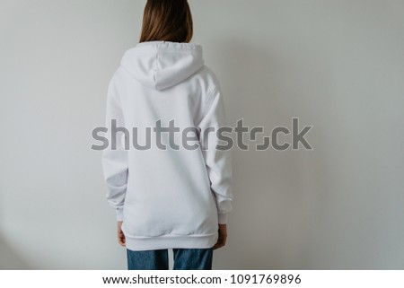 Pretty young fit girl wearing blank white hoodie with copy space for your logo or design, mock-up of template sweatshirt, white wall in the background, back view #1091769896