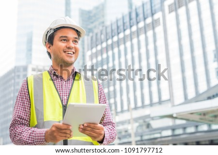 Young handsome asian civil engineer holding tablet looking forward and thinking, planning on construction building background. Evolution construction concept. #1091797712