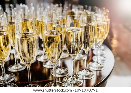 Bottle of sparkling wine with three flute glasses with bubbles floating up on gray backgrounds #1091970791