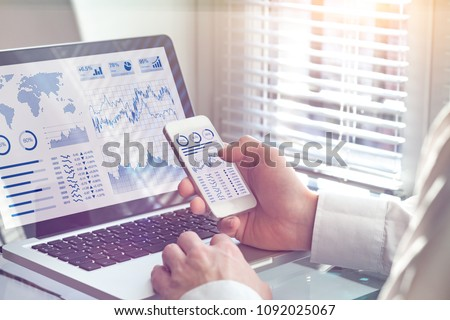 Business analytics dashboard technology on computer and smartphone screen with key performance indicator (KPI) about financial operations statistics and return on investment, office worker #1092025067