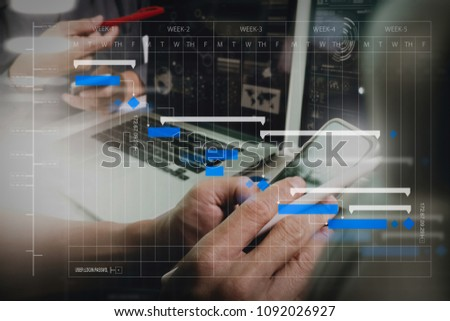 Project manager working and update tasks with milestones progress planning and Gantt chart scheduling diagram.Photo website graphic designer hand working with his team make new project in studio. #1092026927