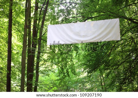 Blank white board banner and green trees