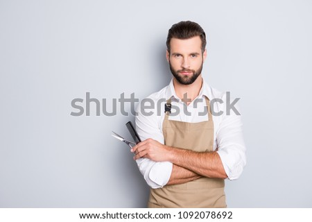 Portrait with copy space, empty place of virile harsh barber having his arms crossed, holding equipments in hand, looking at camera, isolated on grey background #1092078692