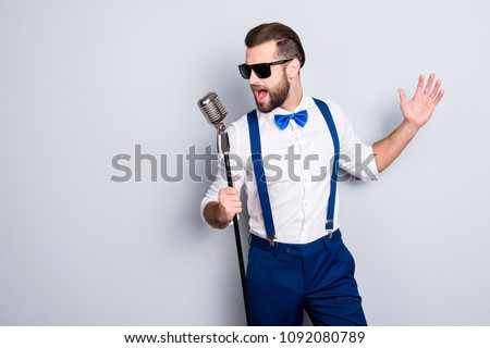 Portrait of handsome attractive singer in blue pants with suspenders and black glasses, singing hit with open mouth in microphone gesture with hand isolated on grey background #1092080789