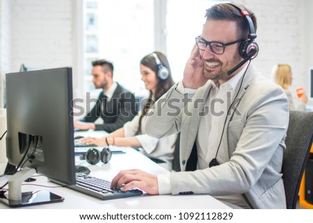 Smiling call center worker with headset giving technical support to customers. #1092112829