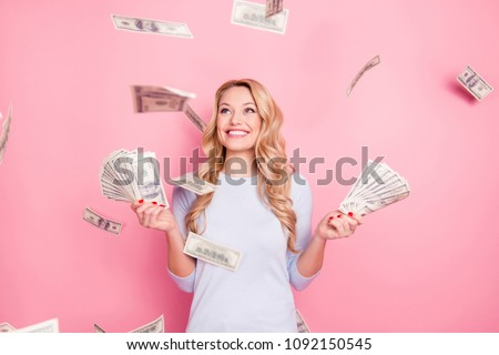 Portrait of pretty charming positive cute successful lucky cheerful girl standing under shower from money having a lot of money in hands isolated on pink background #1092150545