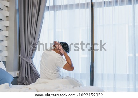 Man stretching in bed after wake up in the morning. #1092159932